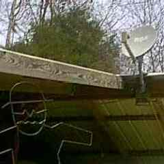 Satellite Dish mounted at this house trailer on their carport.