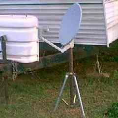 Satellite Dish mounted on a tripod stand in the yard and is moveable at a resort location.