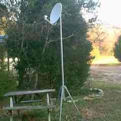 Satellite Dish mounted on a very tall tripod that is movable to get over the trees at a Resort.